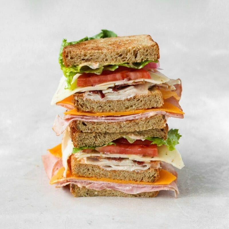 turkey, ham, bacon, cheddar, pepper jack, lettuce, tomato, onion & tangy sriracha mayo on three slices of toasted multi-grain bread